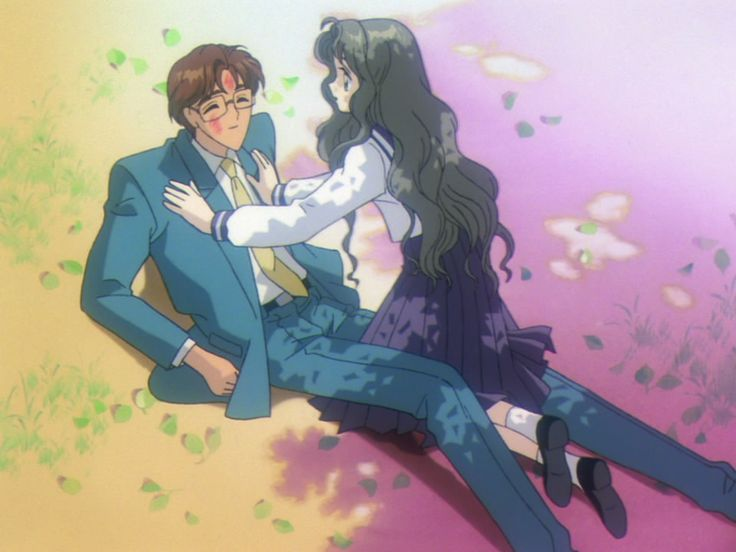 A man in a business suit and glasses is propped up on his elbows on the ground while a teen girl in a school uniform presses her hands to his chest as if she's just fallen into him. She looks concerned, but he's smiling.