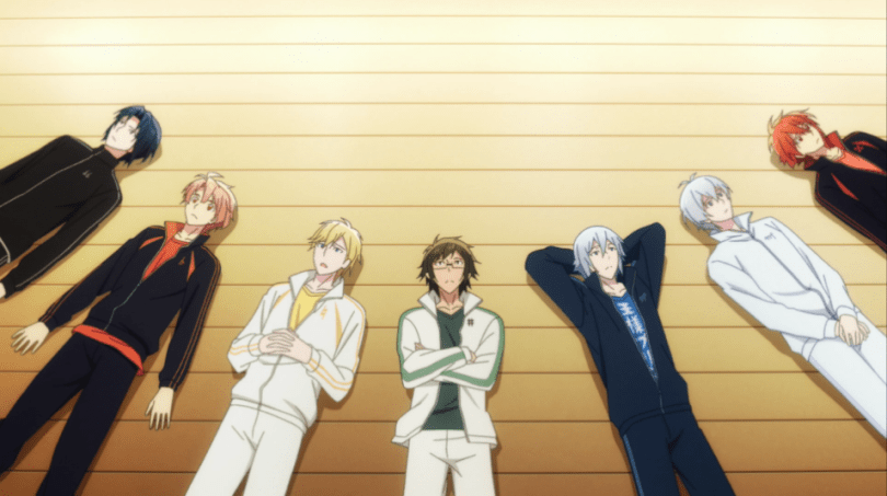 Seven young men (teens/20s) in multicolored track suits lie on a wooden floor, staring up at the ceiling.