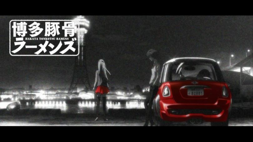 "A black-and-white image of a person in feminine clothing leaning on a railing and looking out over a cityscape while a masculine figure leans against a car. On-screen text says ""Hakata Tonkotsu Ramens."""