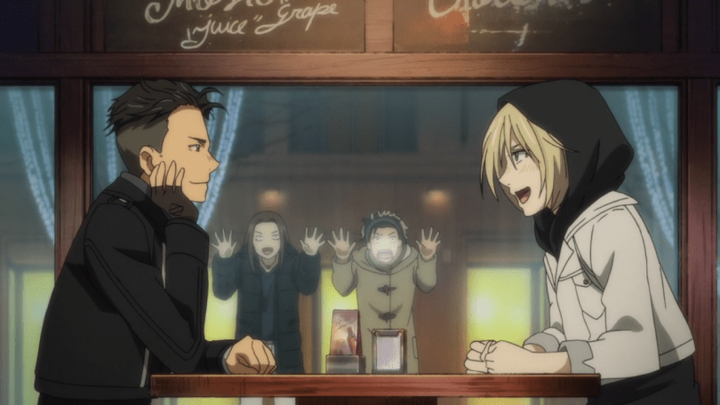 Two teen boys, one with short dark hair and one with mid-length blonde hair and a hoodie, sit at a restaurant table while two women press their faces to the window outside, looking surprised.