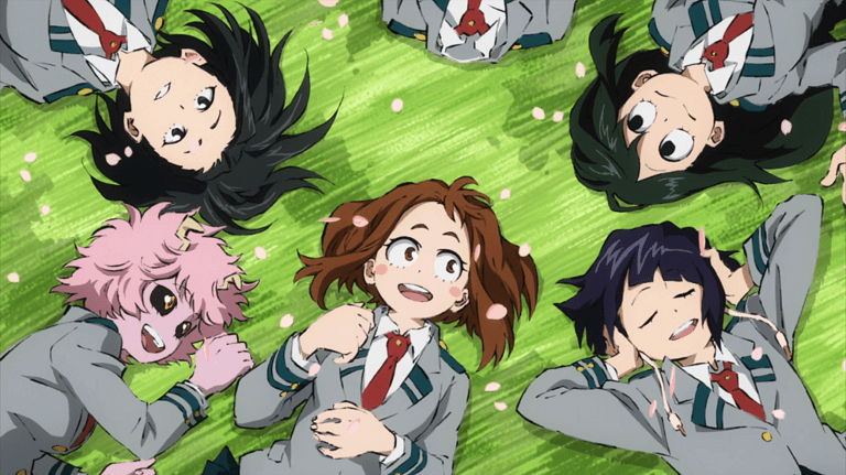 Six young women shown from above as they lie outside on grass. They're all wearing the same school uniform and smiling. One is pink, one has fluffly brown hair, one has short hair and their hands on their ears, one has long hair and a frog-like mouth, one is invisible, and another has dark hair in a ponytail