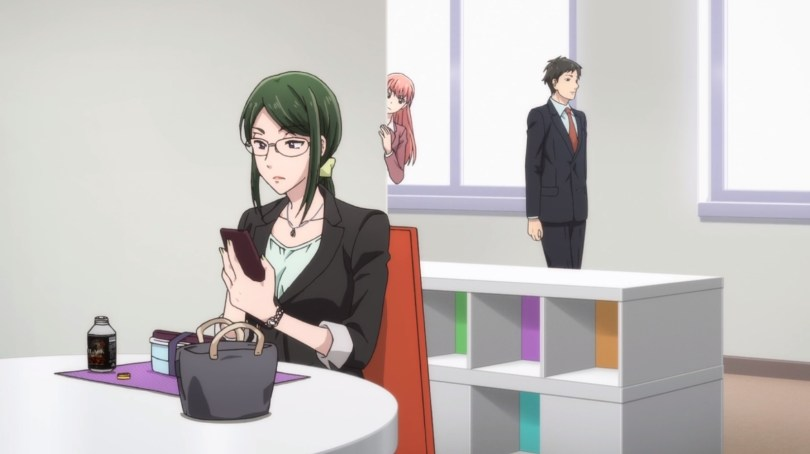 A young woman with long pink-ish hair peeks around the corner of an office at another young woman, this one wearing glasses and looking at her phone.