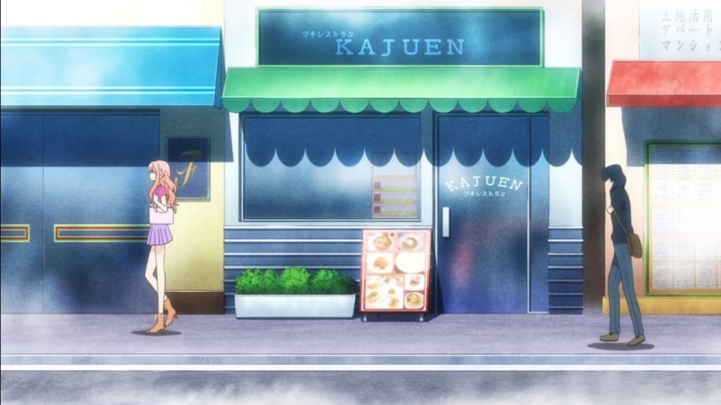 A wide shot of a city street lined with cute restaurants and shops. A teen girl in casual clothes walks forward, with a teen boy in a hoodie following about one-building's-length behind her.