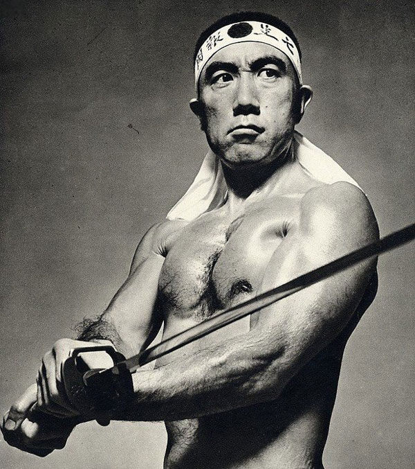 Mishima shirtless and holding a samurai sword