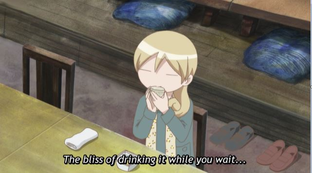 Wakako drinking at a long table. caption: The bliss of drinking while you wait.
