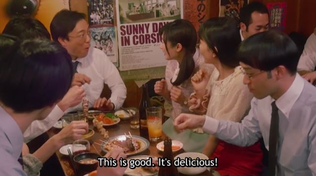 Wakako eating a meal around a table with her coworkers. caption: This is good, it's delicious!