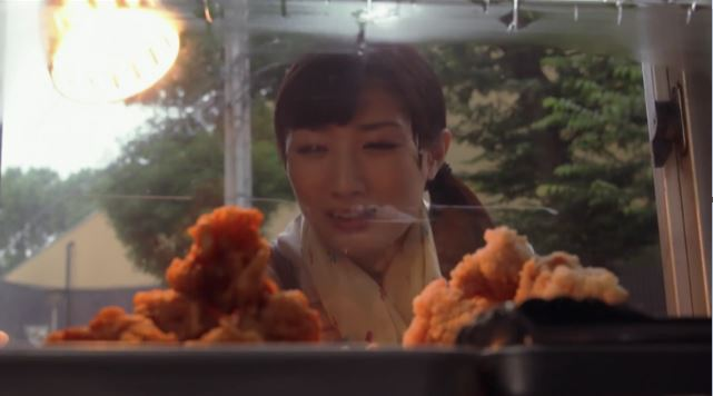 Wakako staring through a window at plates of fried food