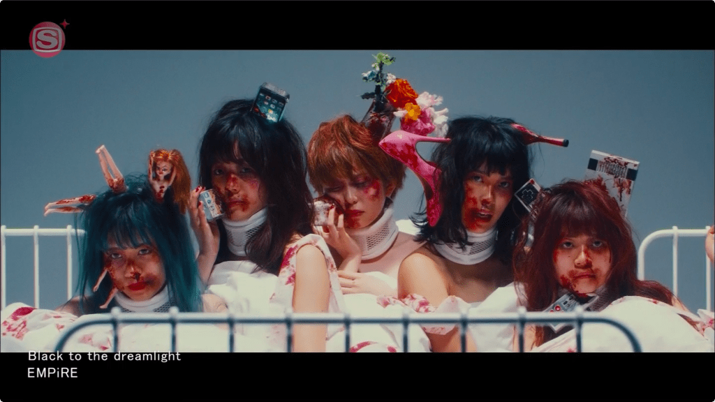 A group of people in a hospital bed, covered in fake blood with modern objects like Barbie dolls, phones, and high-heel shoes sticking out of their heads.