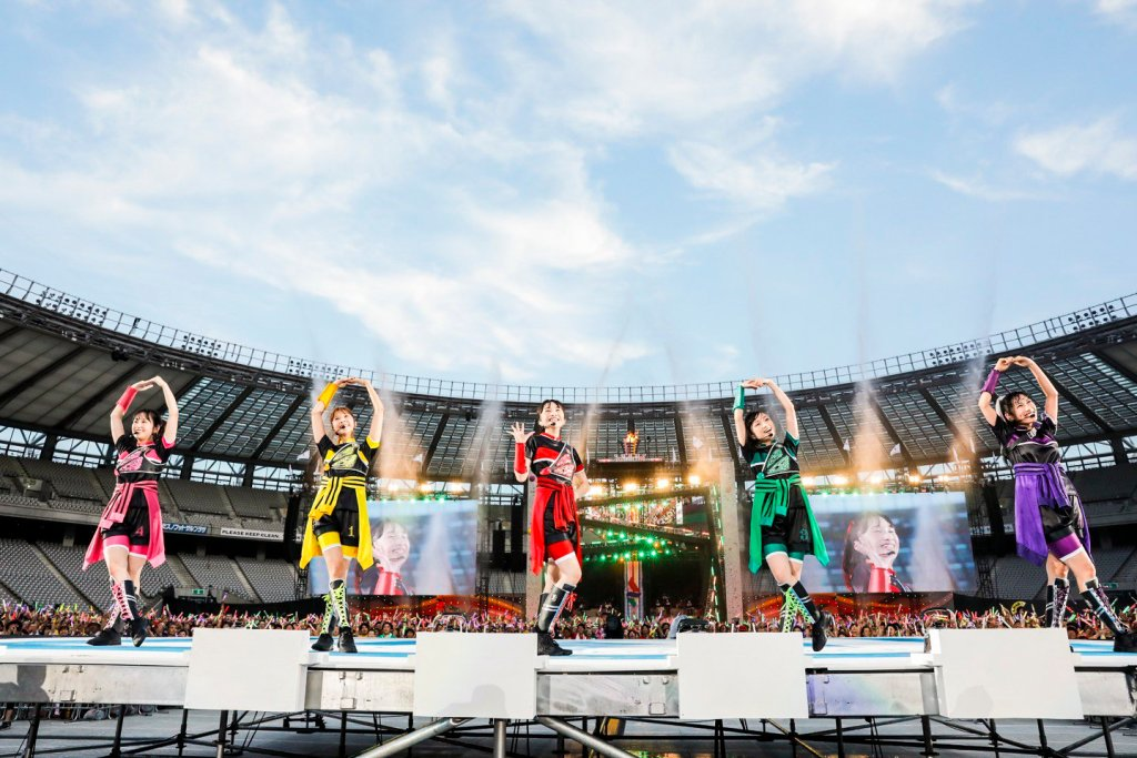 Five women in multicolored outfits stand on a stage in an open-air arena.