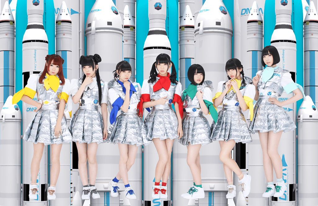 A group of young Japanese women swearing school uniforms made of space blankets stand in front of a bunch of rocket ships.
