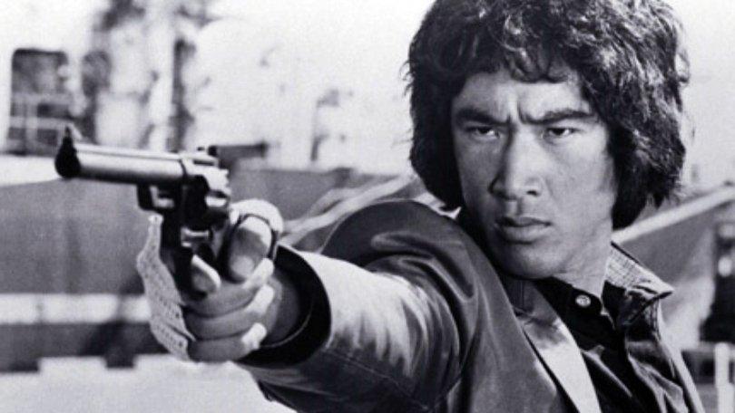 A black-and-white photo of Yusaku Matsuda pointing a gun