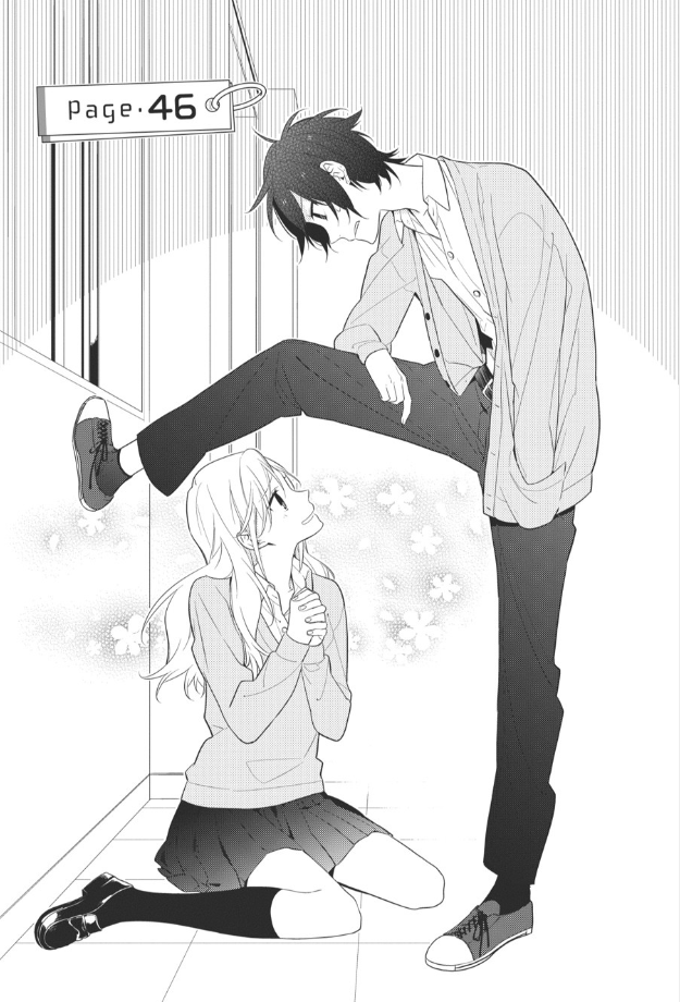 Manga panel of a girl sitting on the ground, hands clasped together, looking up at a boy looming above her. He has one leg up on the wall behind her, as if pinning her in. There are flowers bursting around the girl, suggesting she's enjoying this.