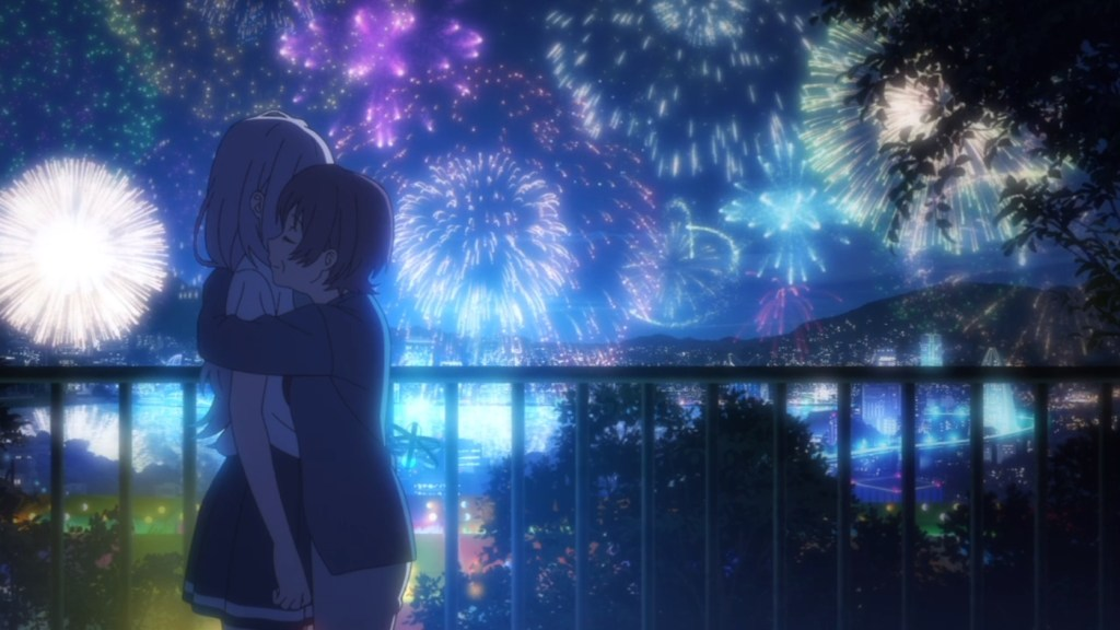 An older woman hugs a teen girl. The two stand in front of a railing, with fireworks bursts in the night sky behind them.
