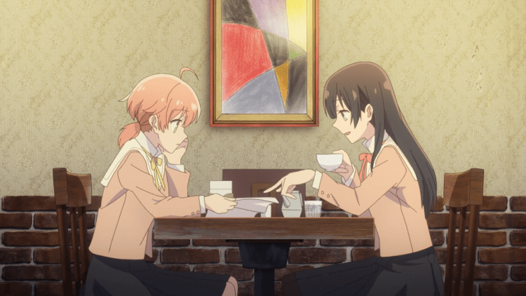 Two high school girls sit at a cafe table. One holds a paper and the other is looking at it, pointing to it.