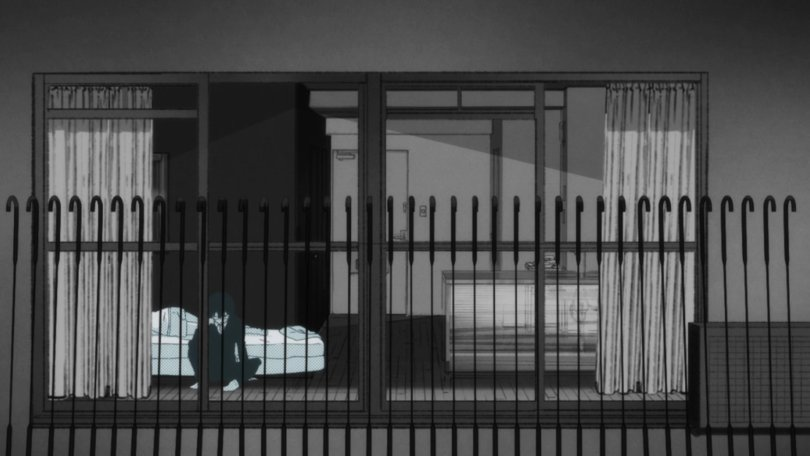 A gray-scale image looking through a window into a room. A boy sits at the foot of a mattress, head in hand. the window is blocked by an iron fence, making it look like the boy is behind bars.