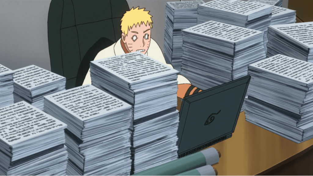 An adult Naruto sitting at a desk behind a laptop and piles of papers, looking frazzled