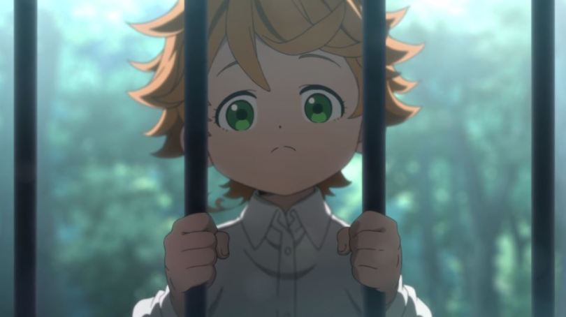 A small redheaded girl staring through a set of bars