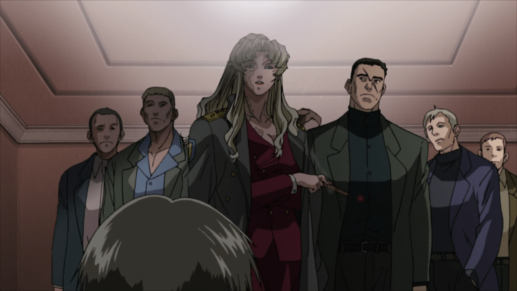 Balalaika surrounded by a group of gangsters, staring down at a seated figure