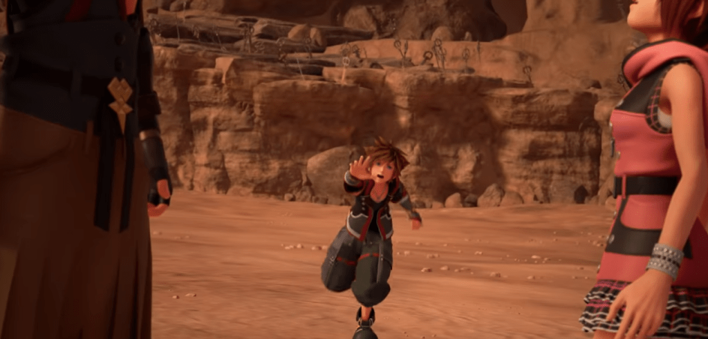 "Sora runs towards the camera. Framed in profile close to the ""lens"" is Kairi on one side and someone in an Organization XII cloak."