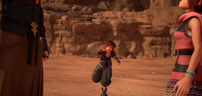 """Sora runs towards the camera. Framed in profile close to the """"lens"""" is Kairi on one side and someone in an Organization XII cloak."""