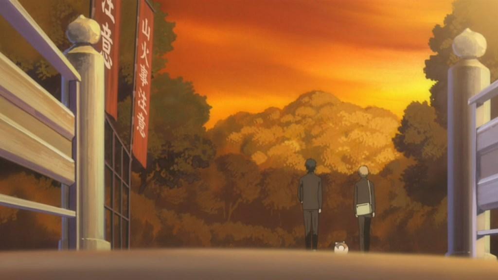 Natsume, Nyanko-sensei, and Tanuma walk over a bridge at sunset, their backs to the camera.