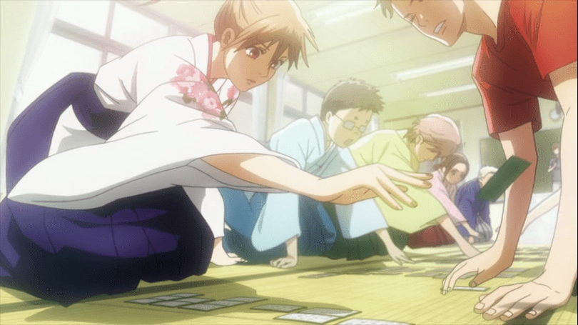 Chihaya in a kimono sits across from Sudo and takes a karuta card from him. Her teammates sit beside her, also going after cards in a match.