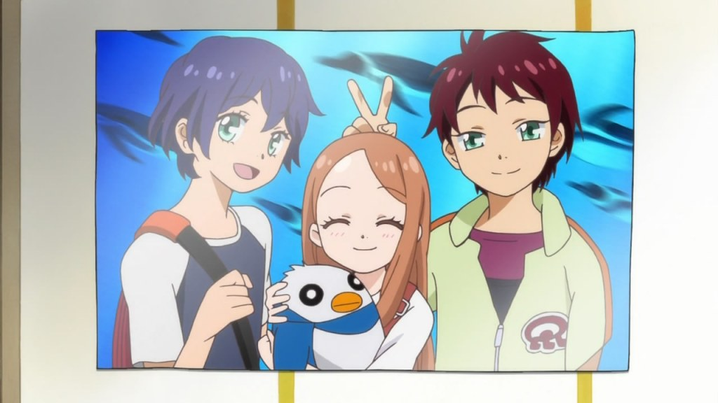 A photo of Kanba, Shouma, and Himari poses in front of a tank of penguins at an aquarium. Himari is holding a plush penguin and Kanba is giving her rabbit ears.