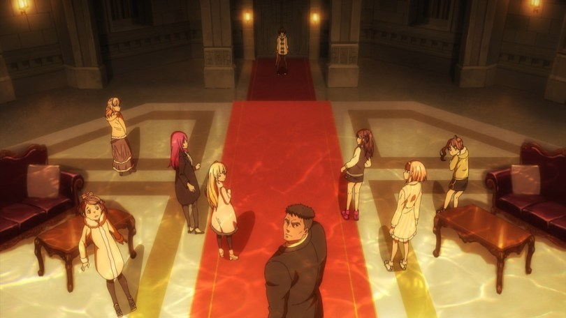 Eight young women stand before a man. A wall glows behid them.