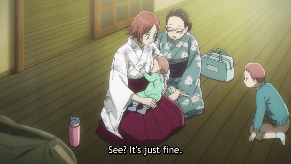 Inokuma holding her son in her hakata, comforted by Mrs. Oe. subtitle: See? It's just fine.