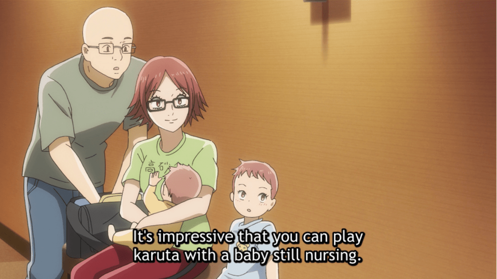 Inokuma sitting with her family getting ready to nurse. subtitle: It's impressive that you can play karuta with a baby still nursing.
