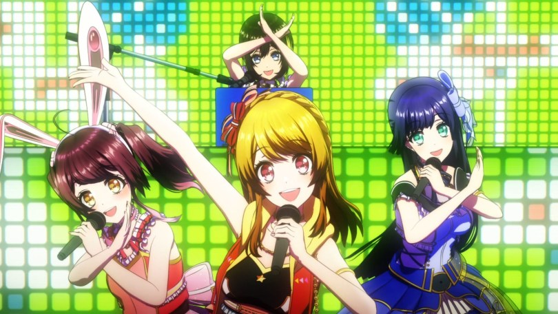 The four members of Happy Around pose happily in front of a blinking LED screen