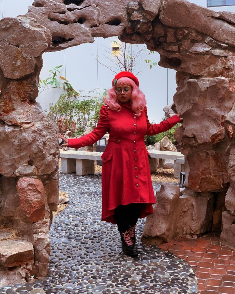 Photo of Jaded Island, with pink hair and a red coat and beret combo