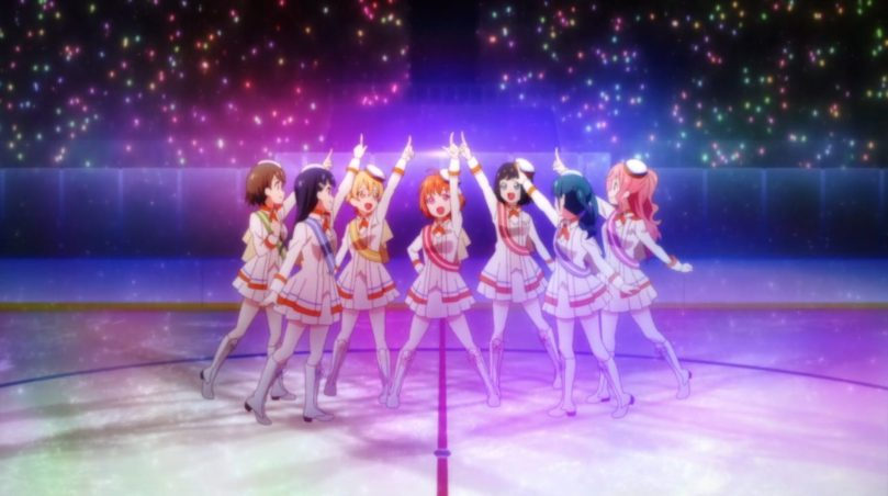 Seven costumed girls doing a choreographed dance against a glittery backdrop, standing on an ice rink