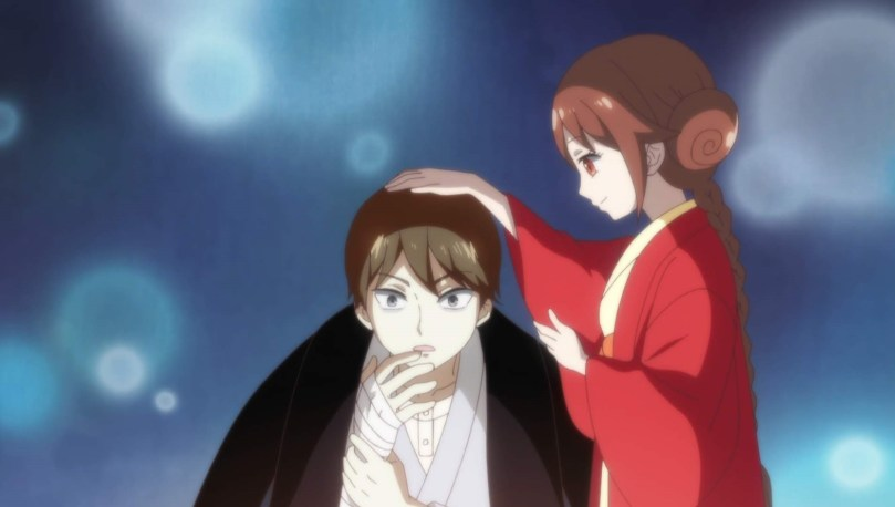 Yuzuki pats a surprised Tamahiko's head as he holds his bandaged right hand to his face.