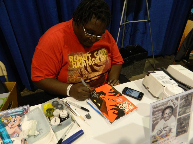 Frankie B. Washington signs the book