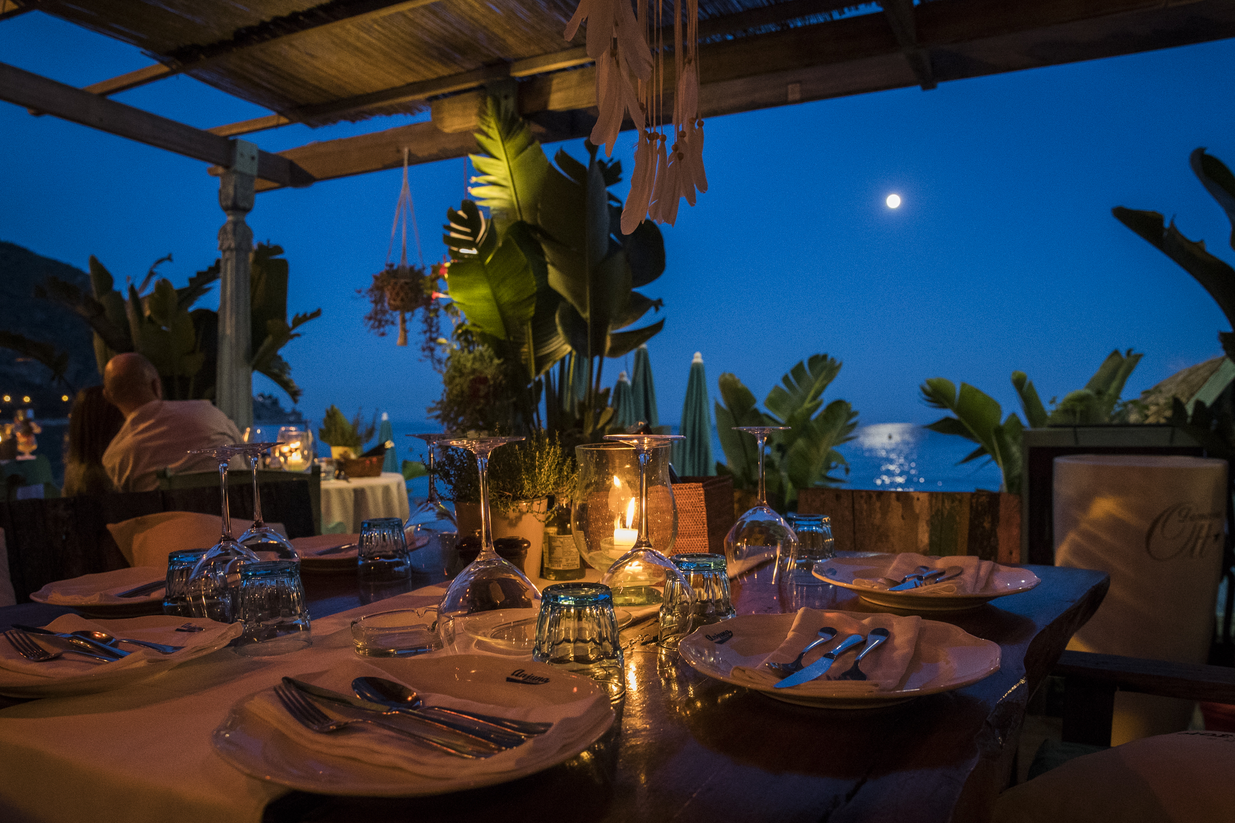 Romantic dinner table at sundown at Anjuna, a beach restaurant by the Mediterranean sea.