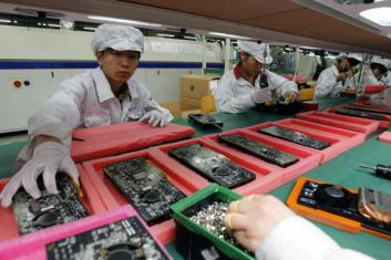 FILE - In this May 26, 2010 file photo, staff members work on the production line at the Foxconn complex in the southern Chinese city of Shenzhen. The company that makes Apple's iPhones suspended production at a factory in China on Monday, Sept. 24, 2012, after a brawl by as many as 2,000 employees at a dormitory injured 40 people. The fight, the cause of which was under investigation, erupted Sunday night at a privately managed dormitory near a Foxconn Technology Group factory in the northern city of Taiyuan, the company and Chinese police said. (AP Photo/Kin Cheung, File)