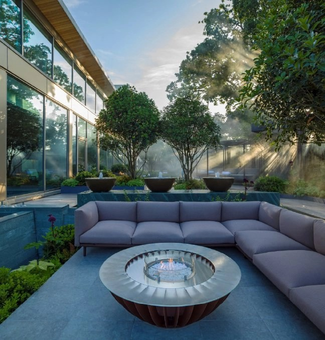 Outdoor seating area around firepit, next to infinity spa pool designed by Ann-Marie Powell Gardens