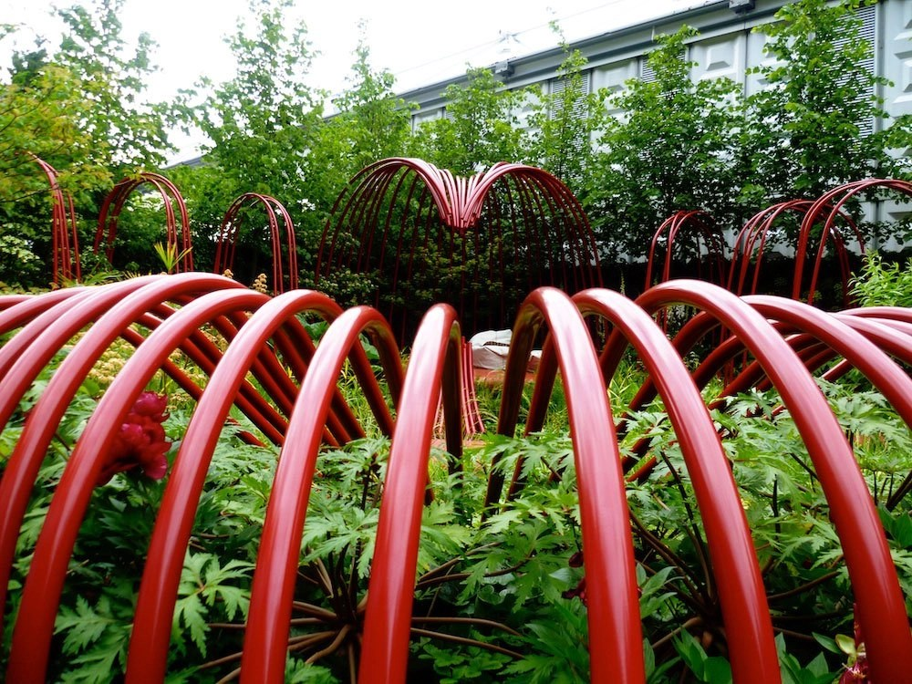 Vivid red curves design representing the movement of blood through the body offset by contrasting green foliage