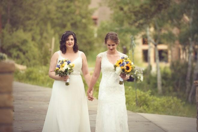 brides walking toward ceremony site Della Terra