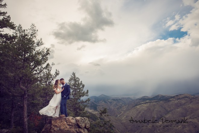 epic image of couple on tall rock in front of an overlook