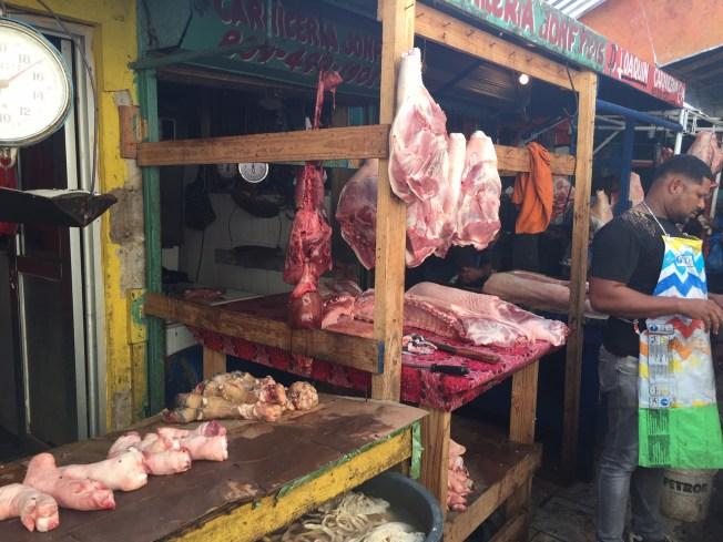 En man med färgad hy står med förkläde framför ett köttmarknadsstånd.