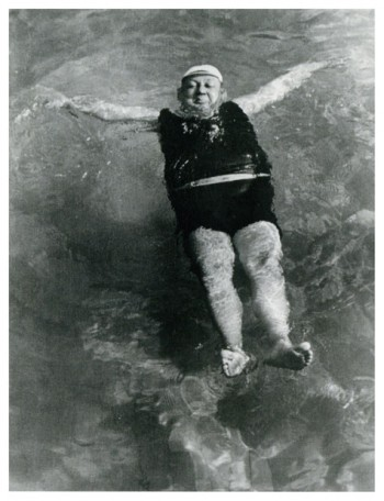 Black and white Photograph of a man floating on his back in a swimming pool.