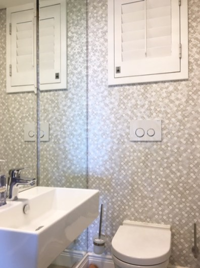 Guest loo decorated with wallpaper and wall to wall bevelled mirrors