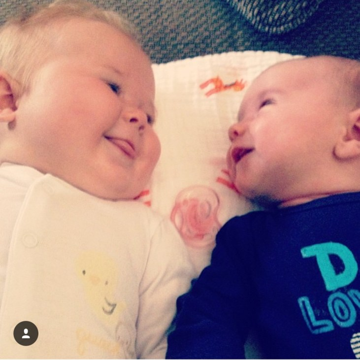 a light skinned baby girl and a light skinned baby boy laying down, looking at each other a smiling