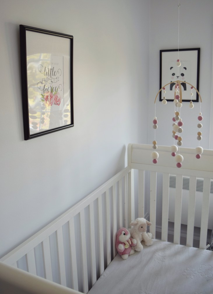 view of crib and prints on the wall, print reads 'though she be but little she is fierce' other print of a panda, there is a delicate mobile hanging above the crib in the baby girl nursery