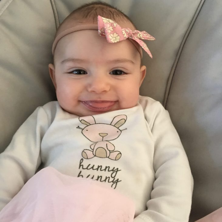 """5 month old light skinned baby girl smiling with her tongue out, wearing a pink bow on her head and a shirt that says """"hunny bunny"""""""