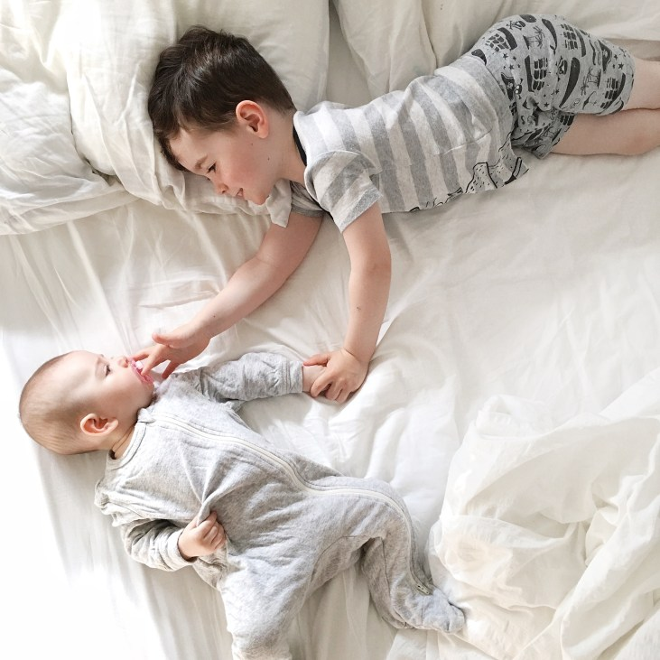 a four year old light skinned boy laying on a bed with his 5 month old light skinned sister, he is helping her by putting a pacifier in her mouth