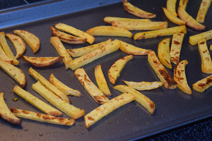 a baking sheet with cooked Rutabaga French Fries on it by Erica Schott