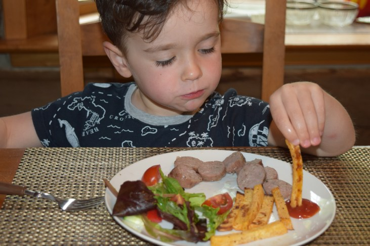 a light skinned 4 year old boy dipping his rutabaga french fries in ketchup